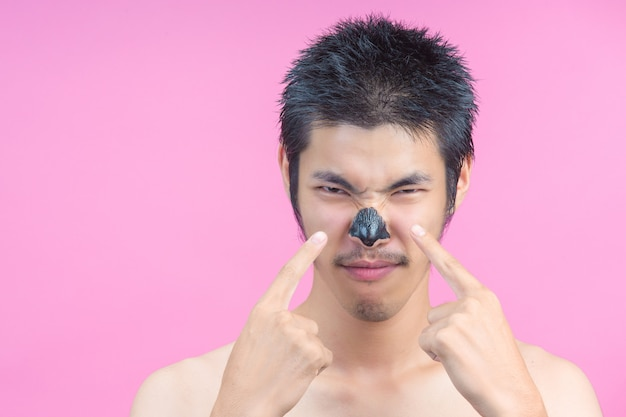 The young man uses his finger to point at the black cosmetic, on the mucus and the pink .