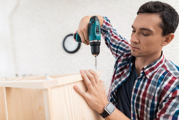 Young man uses tools for furniture.
