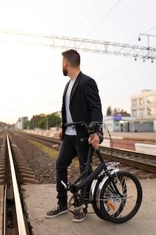 Молодой человек, использующий складной велосипед в городе