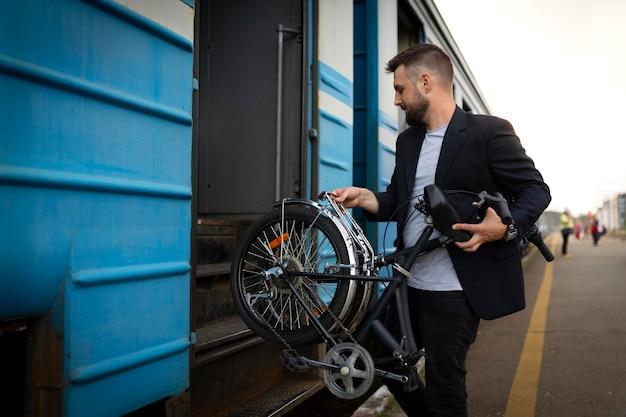 기차로 여행하는 동안 접이식 자전거를 사용하는 청년