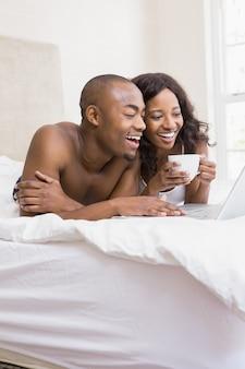 Молодой человек, используя ноутбук и женщина, держащая чашку кофе