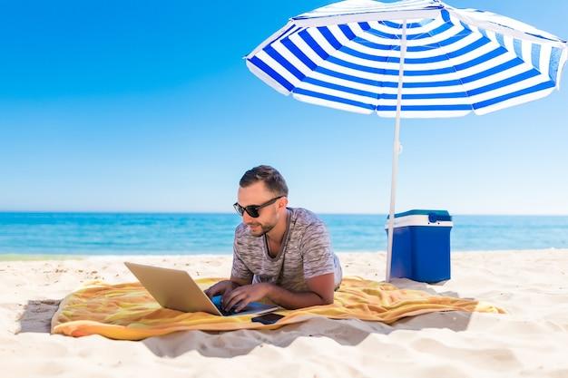 Молодой человек с помощью портативного компьютера на пляже под солнечным зонтиком