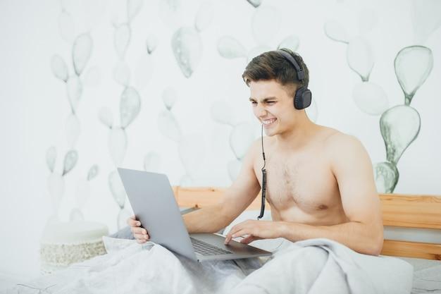 Молодой человек, используя ноутбук в постели