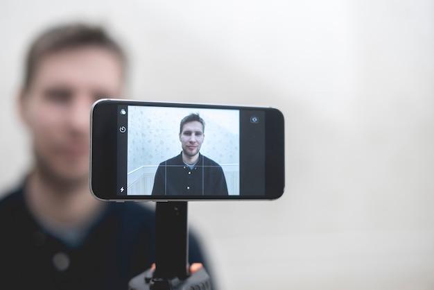 Молодой человек разговаривает по телефону в онлайн-видеозвонке