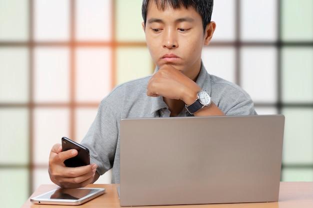 インテリアの建物でスマートフォンとコンピューターのラップトップを使用して若い男。