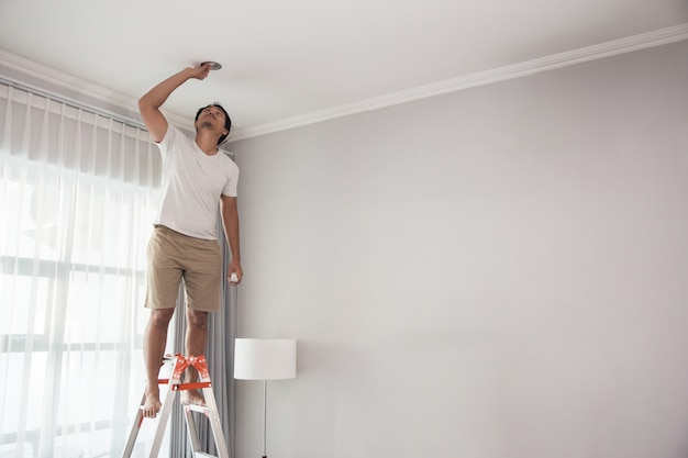 自宅の居間に照明を設置するために階段を使用して若い男