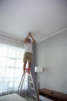 집에서 거실에 조명을 설치하기 위해 계단을 사용하는 젊은 남자