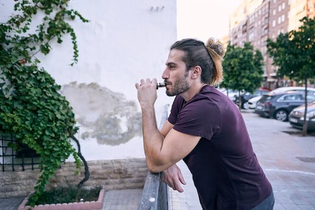 路上で電子タバコを使用している若い男