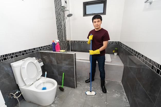 ブラシを使用してバスルームのタイルを掃除する若い男
