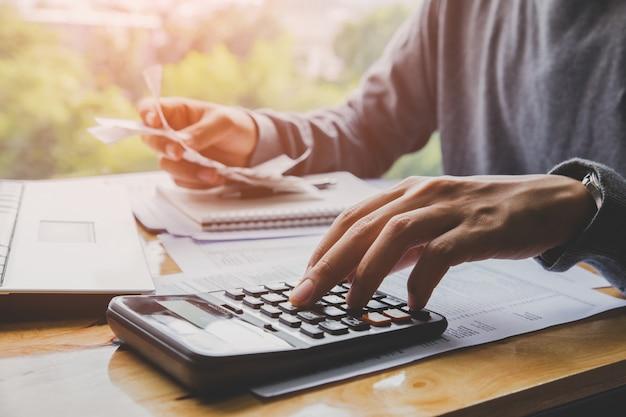 Молодой человек, используя калькулятор и рассчитать счета в домашнем офисе.