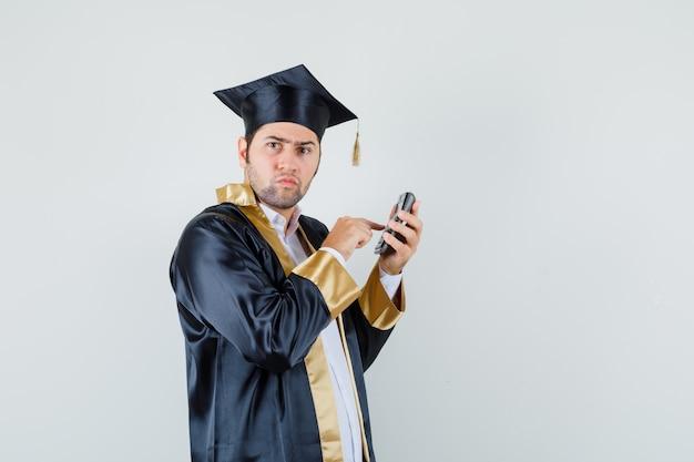 Молодой человек с помощью калькулятора в форме выпускника и задумчивый вид спереди.