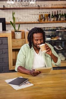 Молодой человек с помощью цифрового планшета в кафетерии