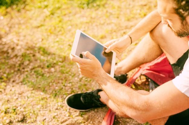 야외에서 디지털 태블릿을 사용 하여 젊은 남자