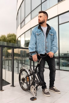 Giovane che utilizza una bicicletta pieghevole in città