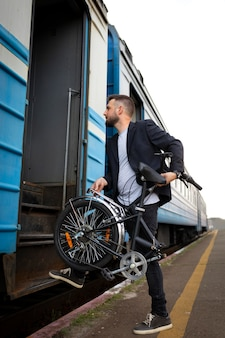 Young man using a folding bike while traveling by train