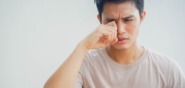 Young man using hand to rubs eye after feeling uncomfortable sensation