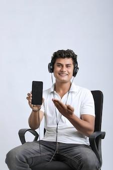 ヘッドフォンを使用して、白い背景の上のスマートフォンを表示している若い男。