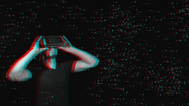 A young man using high-tech virtual reality glasses. with space for text. black and white with 3d glitch virtual reality effect