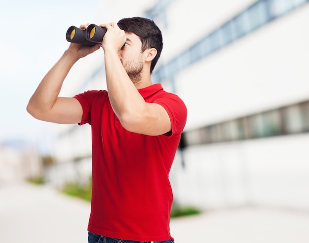 Young man using his binoculars