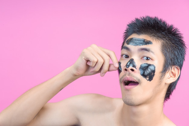A young man using his hands to remove black cosmetics on his face on a pink .