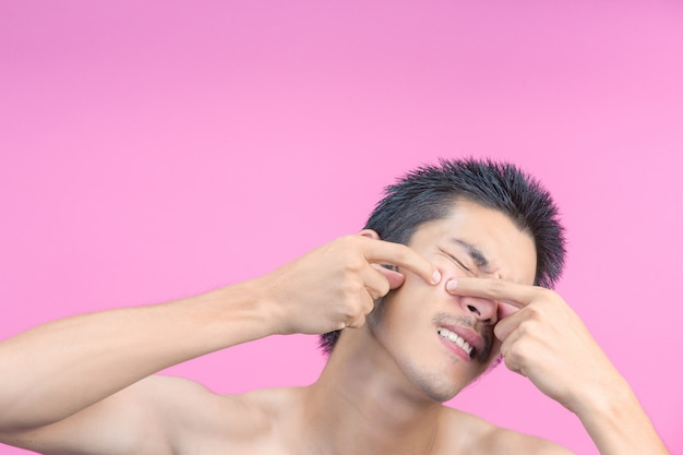 The young man using his hands to squeeze pimples on his face and the pink .