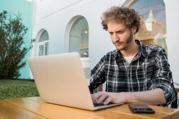 コーヒーショップで彼のラップトップを使用して若い男。