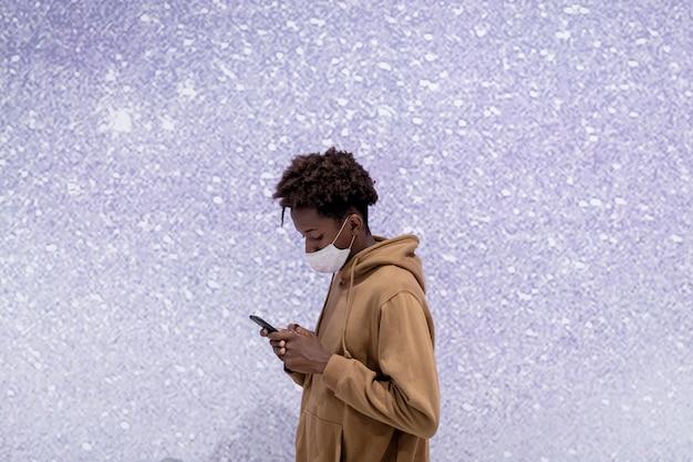 보라색 반짝이 벽으로 자신의 전화를 사용하는 젊은 남자