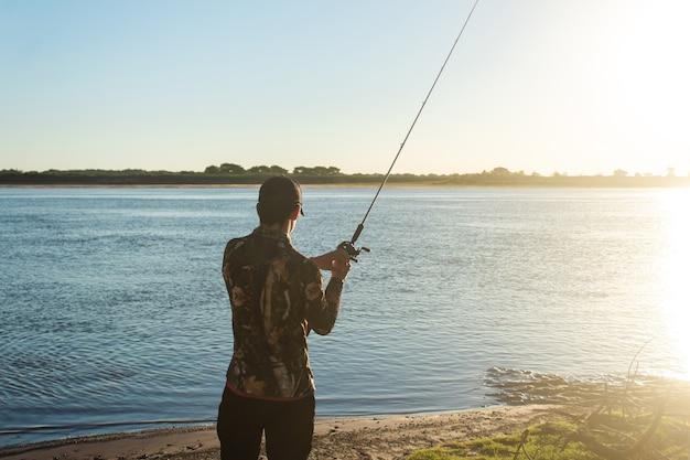 Молодой человек с удочкой ловит рыбу в реке.