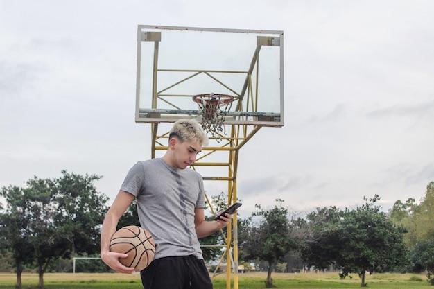 放棄されたバスケットボールコートから彼のスマートフォンを使用している若い男。