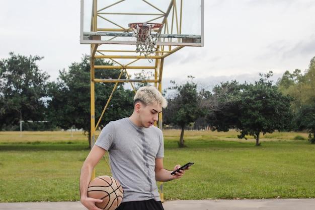 放棄されたバスケットボールコートで彼のスマートフォンを使用している若い男。