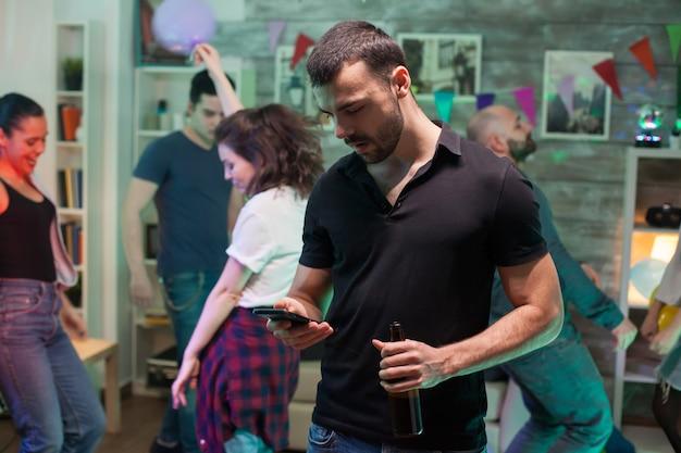 모든 아름다운 여성이 배경에서 춤을 추는 동안 젊은 남자는 파티에서 스마트폰을 사용합니다.