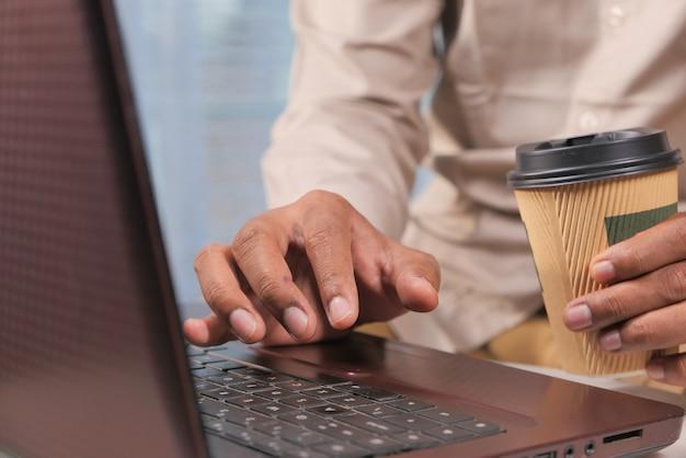 Молодой человек с помощью ноутбука и пить кофе.