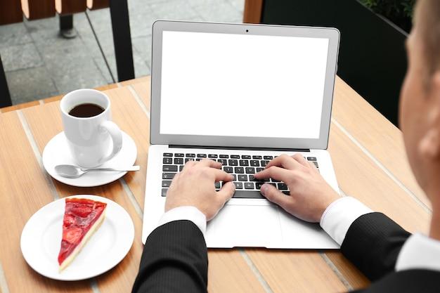 テーブルでラップトップを使用して若い男 Premium写真