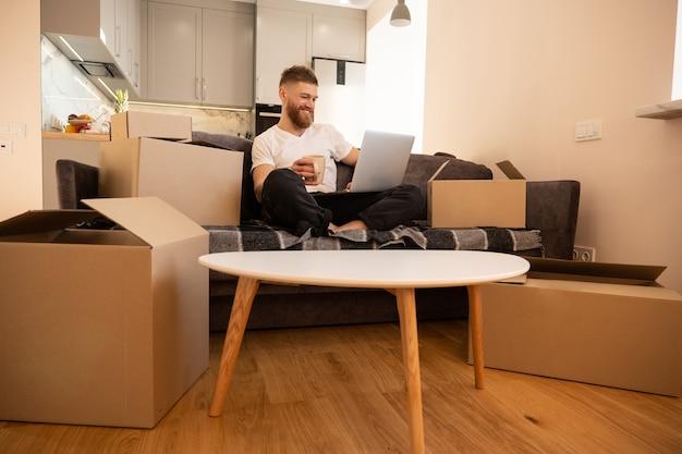 Молодой человек с помощью портативного компьютера и пить чай или кофе. улыбающийся европейский бородатый парень, сидящий на софе. картонные коробки с вещами. концепция переезда в новую квартиру. интерьер однокомнатной квартиры