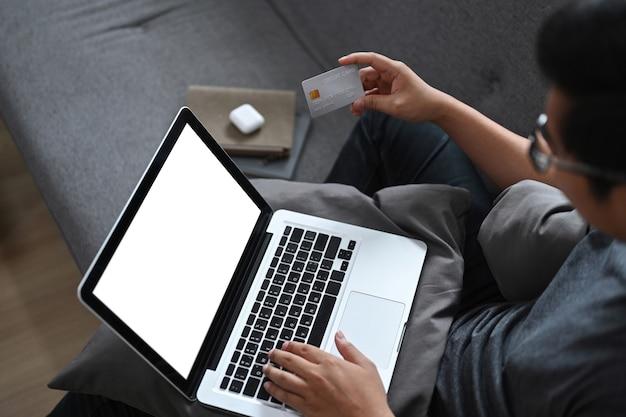 노트북 컴퓨터를 사용하고 집에서 온라인 쇼핑을 위해 신용 카드를 들고 있는 젊은 남자.