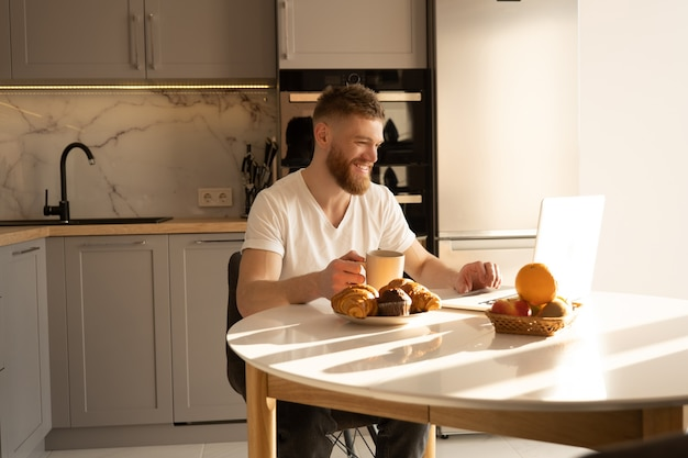 Young man using laptop computer and drinking tea or coffee. smiling european bearded guy sitting at table with delicious food. interior of kitchen in modern apartment. sunny morning time