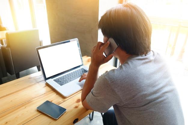 Молодой человек, используя портативный компьютер с пустой экземпляр пространства экрана и вызова мобильного телефона, сидя в кафе, вспышки солнца