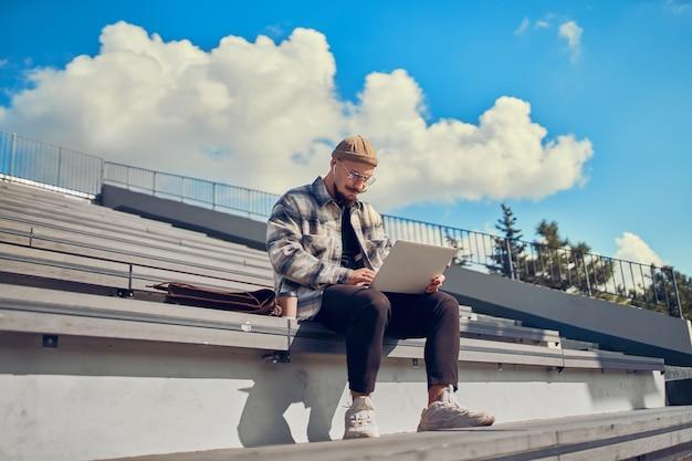 컴퓨터에서 키보드 채팅으로 온라인 야외 타이핑 작업을 하는 노트북 프리랜서를 사용하는 청년