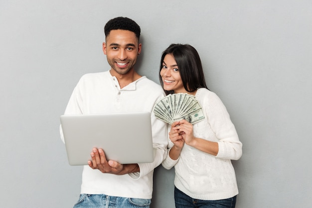 Young man using laptop near his woman with money