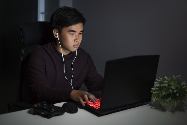 Young man using laptop on table at night