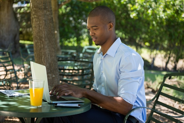 Молодой человек с помощью ноутбука, сидя за столом в ресторане