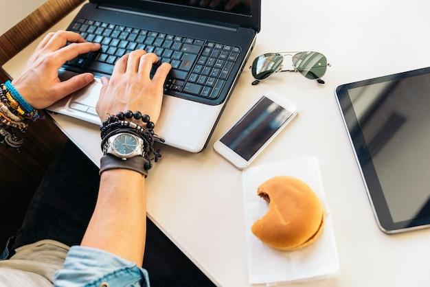 점심을하는 동안 노트북을 사용하는 젊은 남자.