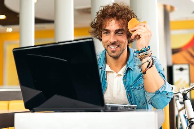 昼食をとりながらノートパソコンを使う若い男。