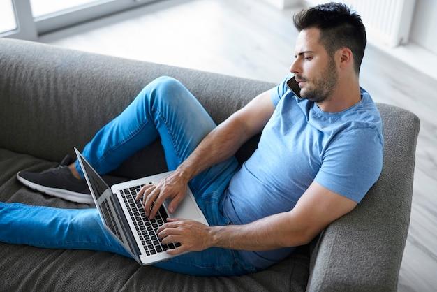 Молодой человек с помощью мобильного телефона и ноутбука в гостиной