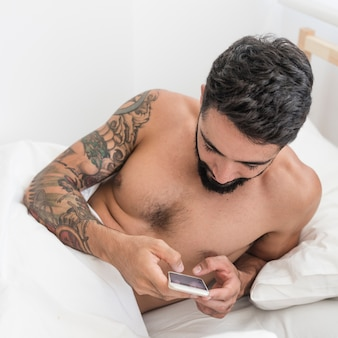 Young man using mobile phone on bed