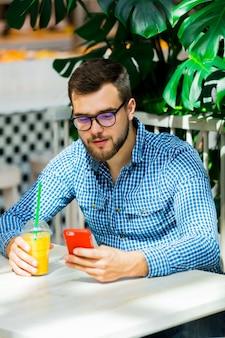 カフェで携帯電話を使用して若い男