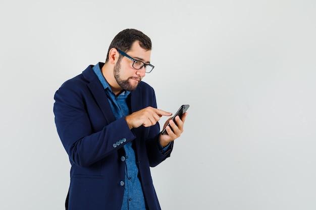 젊은 남자 셔츠, 재킷에 휴대 전화를 사용하고 바쁜 찾고