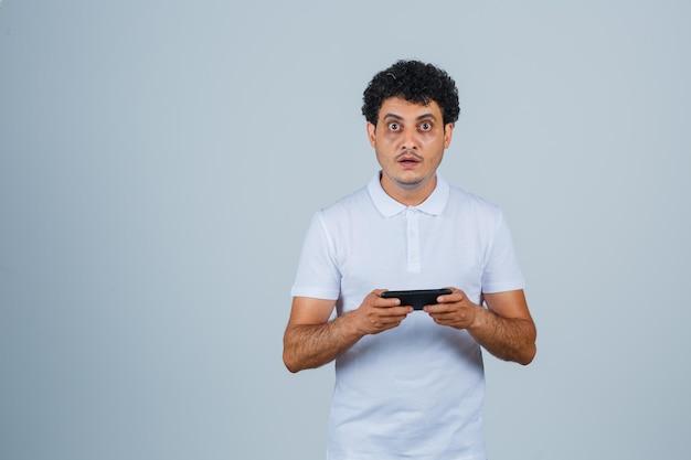 白いtシャツを着て携帯電話を使用して困惑している若い男。正面図。