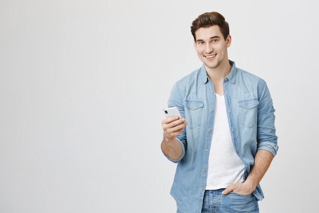 Young man using mobile phone, messaging with friend