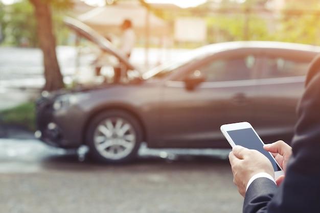 거리에 세분화 된 자동차를 보면서 휴대 전화를 사용하는 젊은 남자